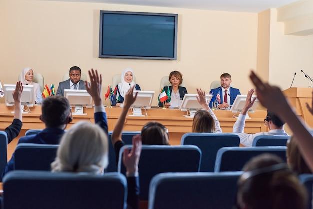 Público em poltronas levantando as mãos para fazer perguntas a delegados interculturais em eventos de negócios ou políticos