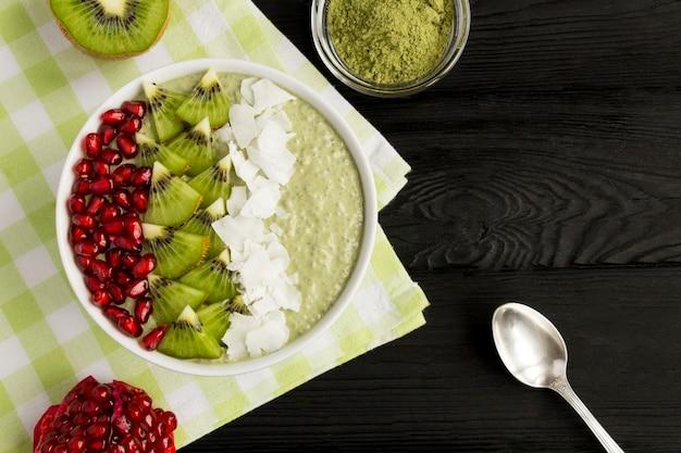 Pudim com chia, chá matcha, kiwi, sementes de romã e flocos de coco na tigela branca sobre a mesa de madeira preta. vista do topo. copie o espaço.