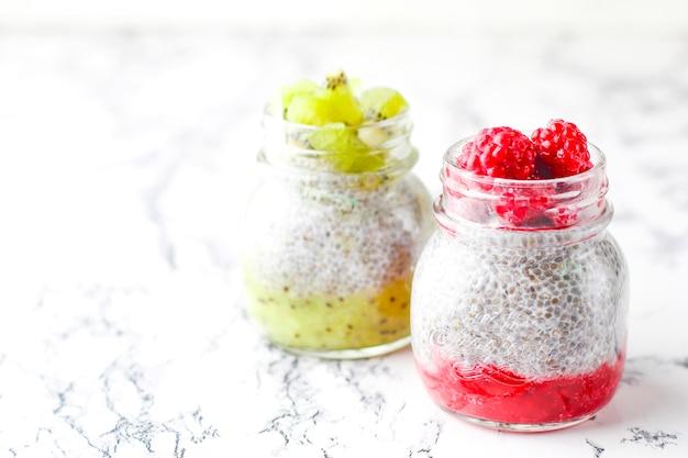 Pudim com frutas, molho de framboesa, molho de kiwi, framboesas congeladas e amoras e fatias de kiwi