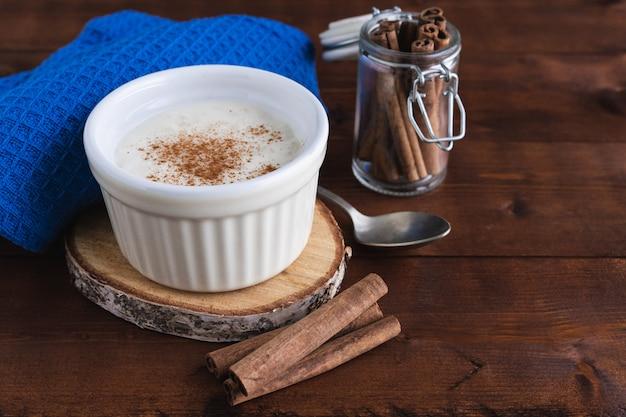 Pudim cremoso de arroz e canela em uma base de madeira. conceito de pastelaria.