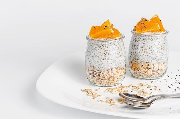 Pudim da semente de chia com laranja e aveia na parede branca. conceito de café da manhã e superalimento. copie o espaço