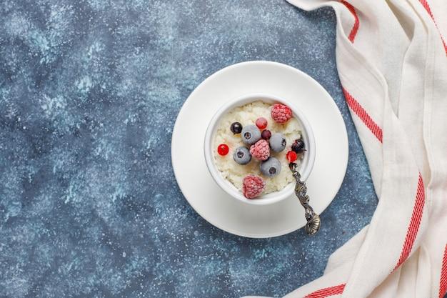 Pudim de arroz com mirtilos congelados e framboesas em tigela branca