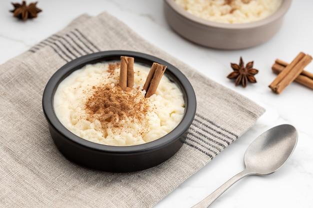 Pudim de arroz cremoso com canela em uma tigela na mesa de mármore branco. sobremesa típica espanhola