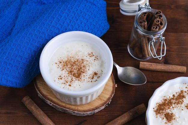Pudim de arroz cremoso e canela numa base de madeira. conceito de pastelaria.