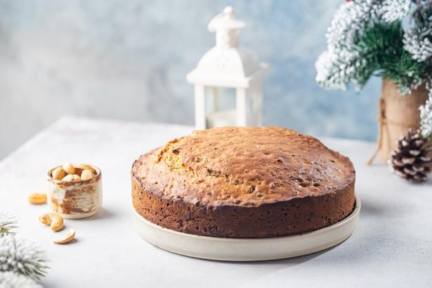 Pudim de bolo de natal tradicional com frutas e nozes com fundo claro de decorações de natal