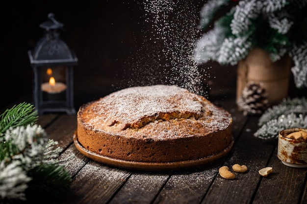 Pudim de bolo de natal tradicional com frutas e nozes com fundo escuro de decoração de natal