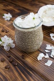 Pudim de café com chia e flocos de coco em uma jarra de vidro no fundo de madeira marrom. localização vertical.