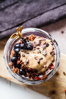 Pudim de chia com frutas, granola e manteiga de amendoim em jar, vista superior