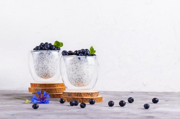 Pudim de chia com hortelã e mirtilos em copos em um carrinho de madeira