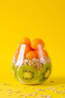 Pudim de chia com kiwis, aveia e melão ou mamão bolas em um copo amarelo