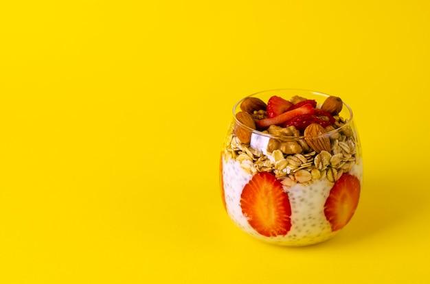 Pudim de chia com morangos, aveia e nozes em um copo amarelo