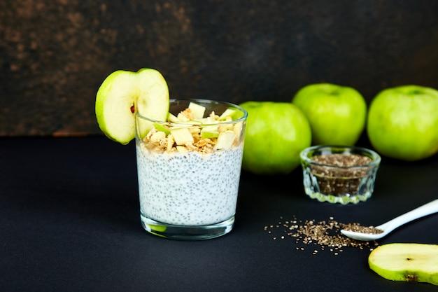 Pudim de chia saudável com maçãs e granola em vidro.