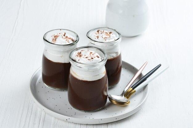 Pudim de chocolate com chantilly e chocolate como cobertura em copos de dose