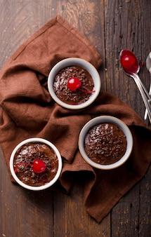 Pudim de chocolate em uma tigela de cerâmica com cerejas