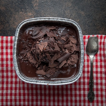 Pudim de chocolate vista superior com colher antiga e pano em placa de alumínio