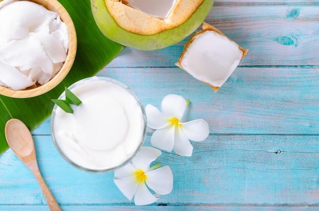 Pudim de coco jovem servido em um copo de vidro decorado com carne de coco parece delicioso nas folhas de bananeira e uma linda mesa de madeira azul. vista do topo.