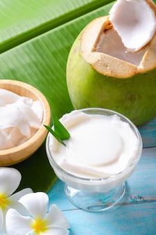 Pudim de coco jovem servido em um copo de vidro decorado com carne de coco parece delicioso nas folhas de bananeira e uma linda mesa de madeira azul.