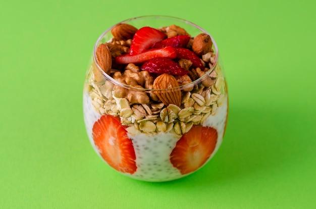 Pudim de iogurte chia com morangos frescos, aveia e nozes em um copo em verde