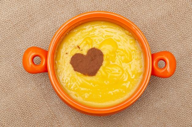 Pudim de milho doce caseiro conhecido no brasil como curau ou canjica nordestina em tigela de cerâmica.