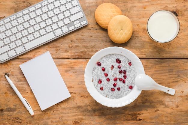 Pudim de semente de chia; biscoitos; smoothie; leite; bloco de anotações; caneta e teclado de computador sem fio no cenário de madeira
