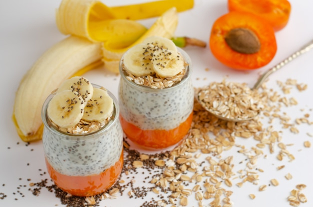 Pudim de sementes de chia com iogurte grego, banana, aveia e damasco fresco.