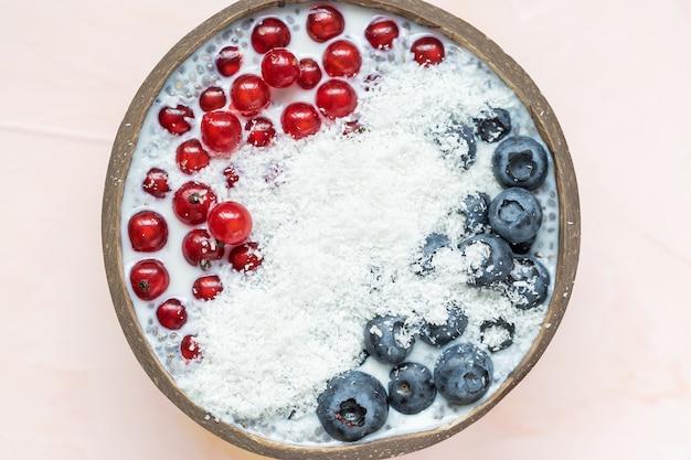 Pudim de sementes de chia com mirtilos, bagas de groselha e flocos de coco em uma tigela