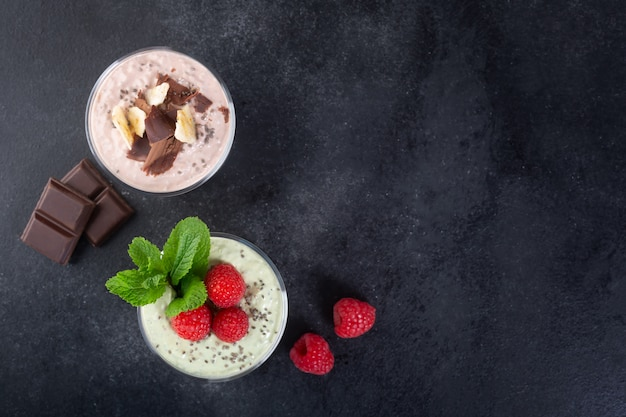Pudim de sementes de chia com três sabores: cacau, matcha e morango com iogurte, chocolate e folhas de hortelã. vista superior com espaço de cópia