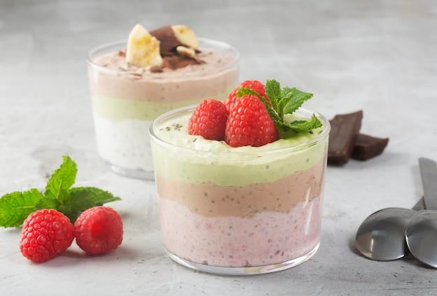 Pudim de sementes de chia com três sabores, cacau, matcha e morango com iogurte, folhas de chocolate e menta, orientação horizontal