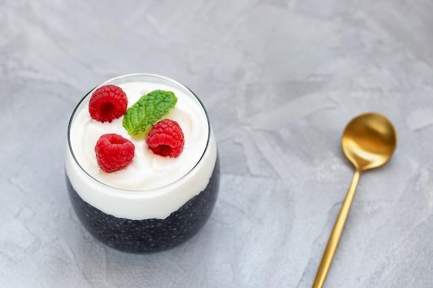 Pudim de sementes de chia preto com leite de amêndoa, iogurte, pó de carvão ativado, sobremesa de framboesas em um copo, colher. superalimento, comida vegetariana, conceito de desintoxicação. parede cinza. copie o espaço, foco seletivo