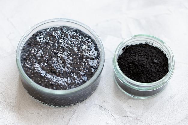 Pudim de sementes de chia preto com pó de carvão ativado, sobremesa em um copo. superalimento, vegan, comida vegetariana, conceito de desintoxicação. parede cinza. copie o espaço, closeup, foco seletivo
