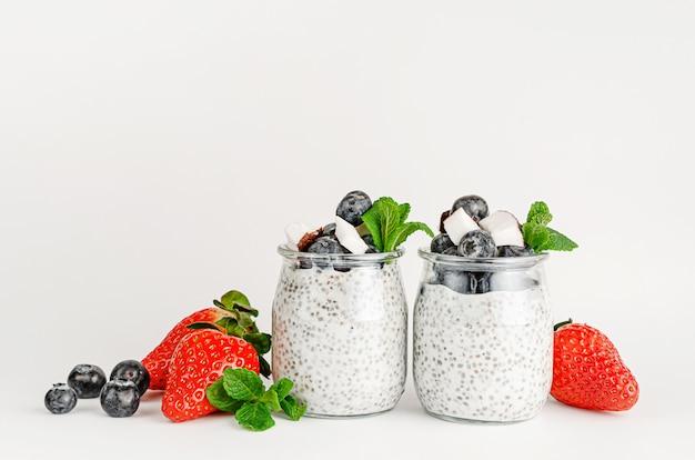 Pudim delicioso de sementes de chia com frutas, coco e hortelã. conceito de alimentação e superalimentos saudáveis. copie o espaço