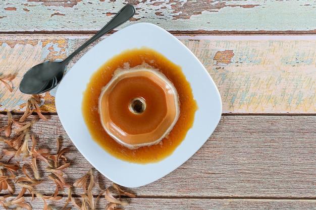 Pudim doce de leite com calda de caramelo, ao lado de sementes voadoras (triplaris americana). um doce tradicional brasileiro.