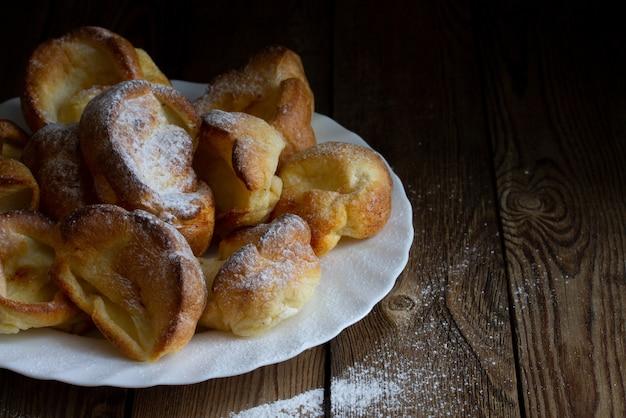 Pudins de yorkshire com açúcar em pó em um prato branco sobre uma mesa de madeira. estilo rústico. copyspace.