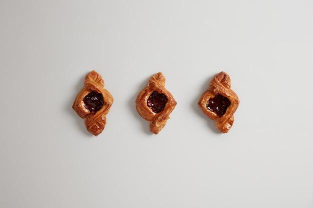 Puff deliciosos pães com geléia isolada na superfície branca. sobremesa saborosa no café da manhã. produtos caseiros assados para quem gosta de doces. nutrição pouco saudável, muito açúcar. receita simples. vista superior, configuração plana