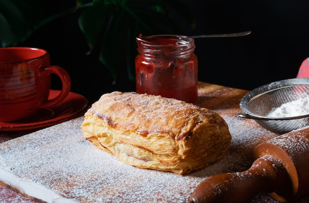 Puff fresco com geléia de ameixa ou groselha na mesa com um copo vermelho e um pote de geléia no fundo preto.