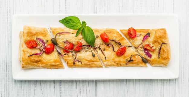 Puff-pizzas com queijo mussarela, tomate cereja e manjericão.
