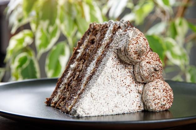 Puff torta de creme em um prato. fundo de folhas verdes.