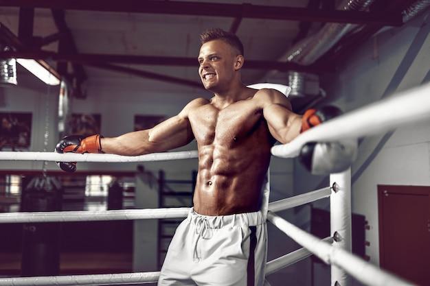 Pugilista profissional musculoso descansando nas cordas no canto do ringue enquanto treinava para a próxima partida