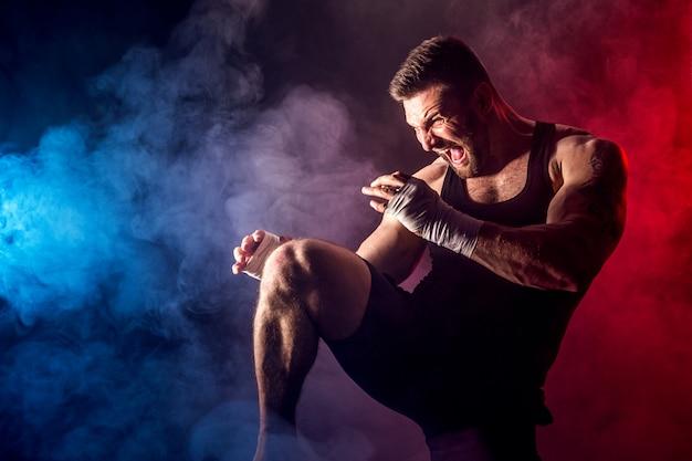 Pugilista tailandês muay do desportista que luta na parede preta com fumo.