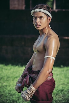 Pugilistas tailandeses enrolam a fita nas mãos e ficam no gramado.