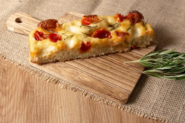 Pugliese focaccia com alecrim, azeite e tomate sobre a mesa de madeira.