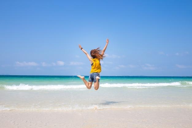 Pulando feliz garota na praia, mulher gosta de vento, liberdade, férias, férias,