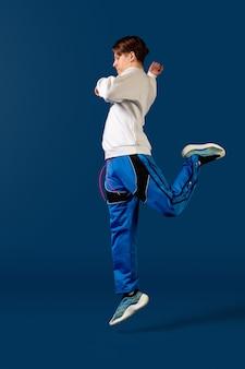 Pulando. jovem à moda antiga dançando isolado no estúdio azul