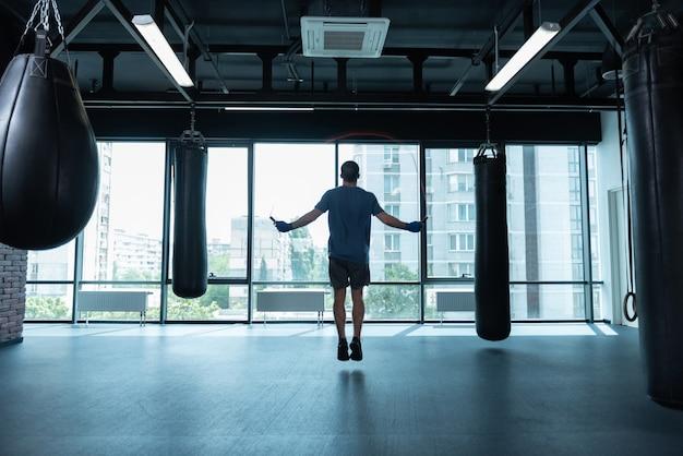 Pular corda. atleta de cabelos negros vestindo camisa azul pulando corda em pé perto da janela com vista para a cidade