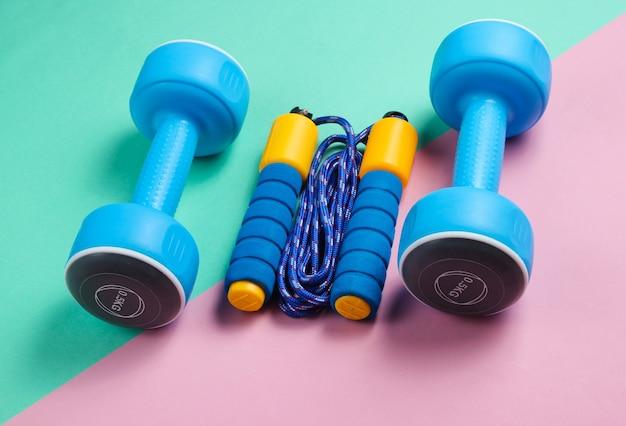 Pular corda colorida, halteres em um fundo rosa azul pastel. conceito de esporte do minimalismo.