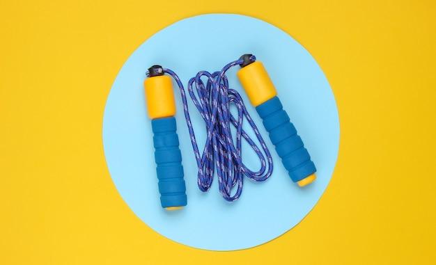 Pular corda em fundo amarelo com um círculo azul pastel no meio. vista do topo. conceito de esporte minimalista.