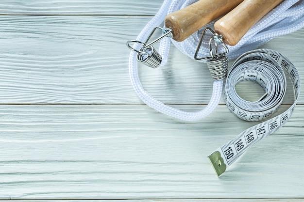 Pular corda enrolada em fita métrica em uma placa de madeira