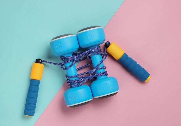 Pular corda enrolada em halteres em tom rosa azul