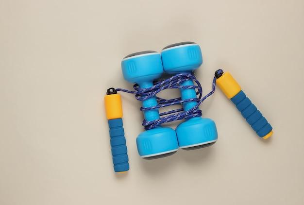 Pular corda enrolada em halteres em um bege