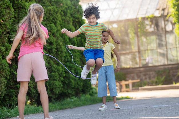 Pular corda. menino enérgico com cabelo escuro encaracolado no salto e duas meninas de cabelos compridos pulando corda perto de arbustos verdes